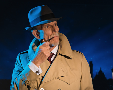 Retro detective man smoking pipe walking in city street at night. Wearing a hat and raincoat. Mysterious atmosphere.