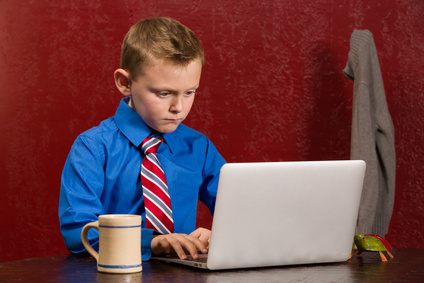Young working boy with tie on computer