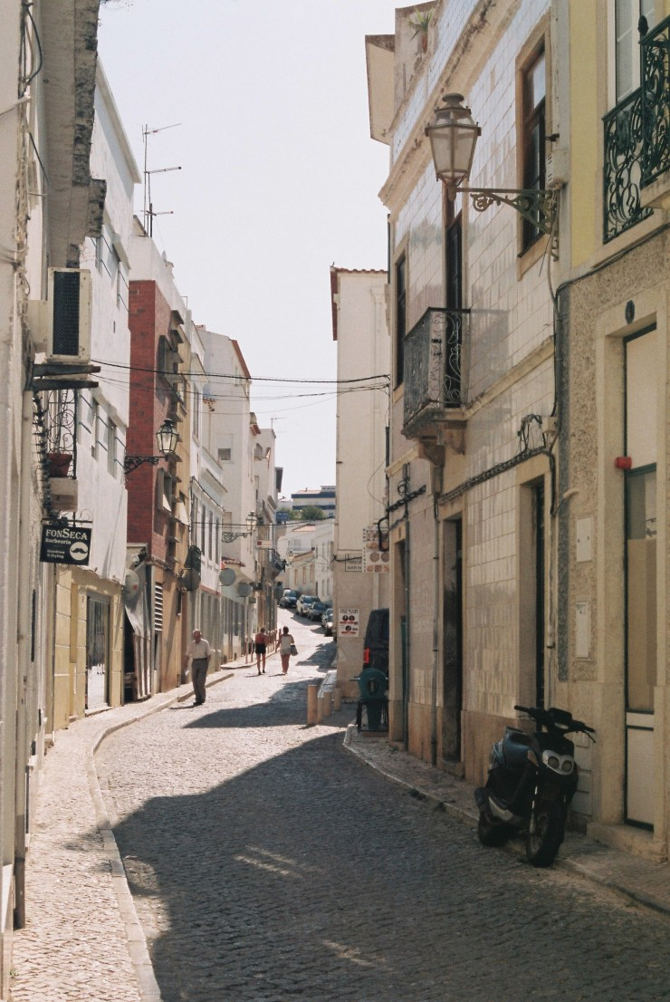 analolgue photo of a street in Lagos, Portugal featuring tiled facades and spiraling metalwork, and old man walks towards the photographer, two females walk away in the distance behind him