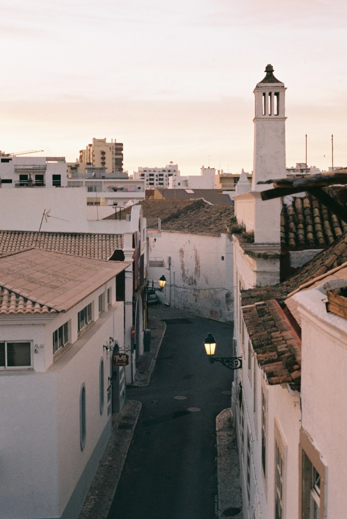 analogue photo of whitewashed walls and red tiled-roofs of Faro under a washed out sky