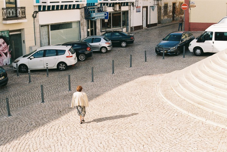 analogue photo of a woman walks over the Portuguese cobbles away from the photographer with her light coat over her shoulders