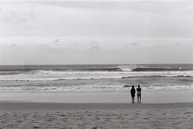 analogue photo of a couple on the beach watch a distant surfer glide across the face of a wave
