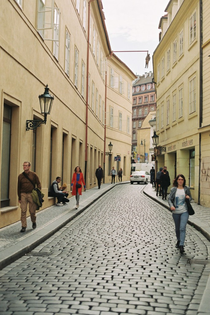 Analogue photo of a Prague street with a sculpture of a man hanging from a pole extended from a 4 storey building
