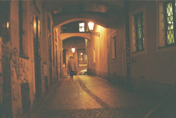 Analogue photo of an old business man walking down a dimly lit alley