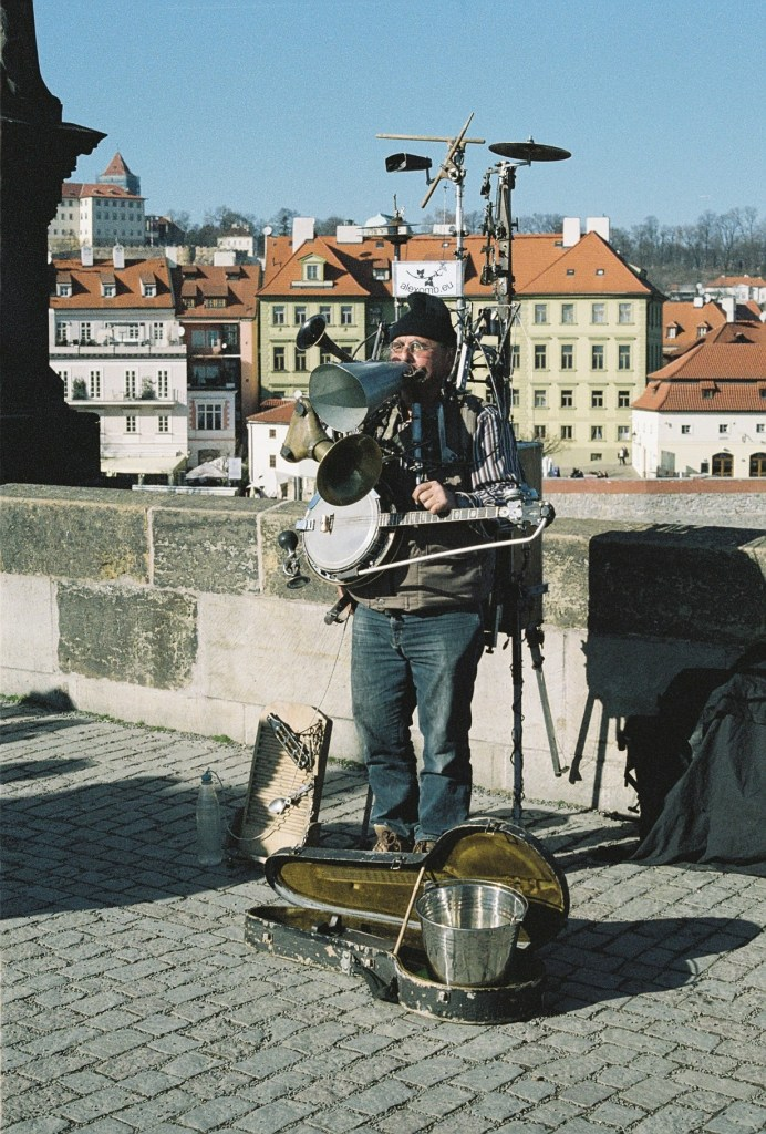 Analogue photo of a one man band with banjo, horns and percussion on his back standing on Charles Bridge, Prague