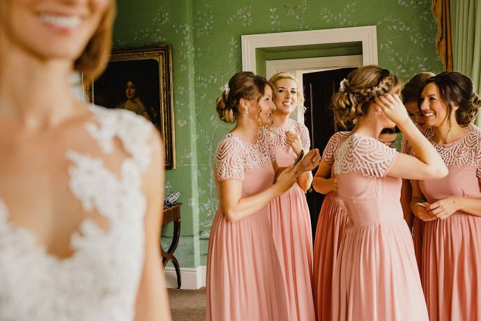 bridesmaids in peach with green wallpaper in the suite at the hotel