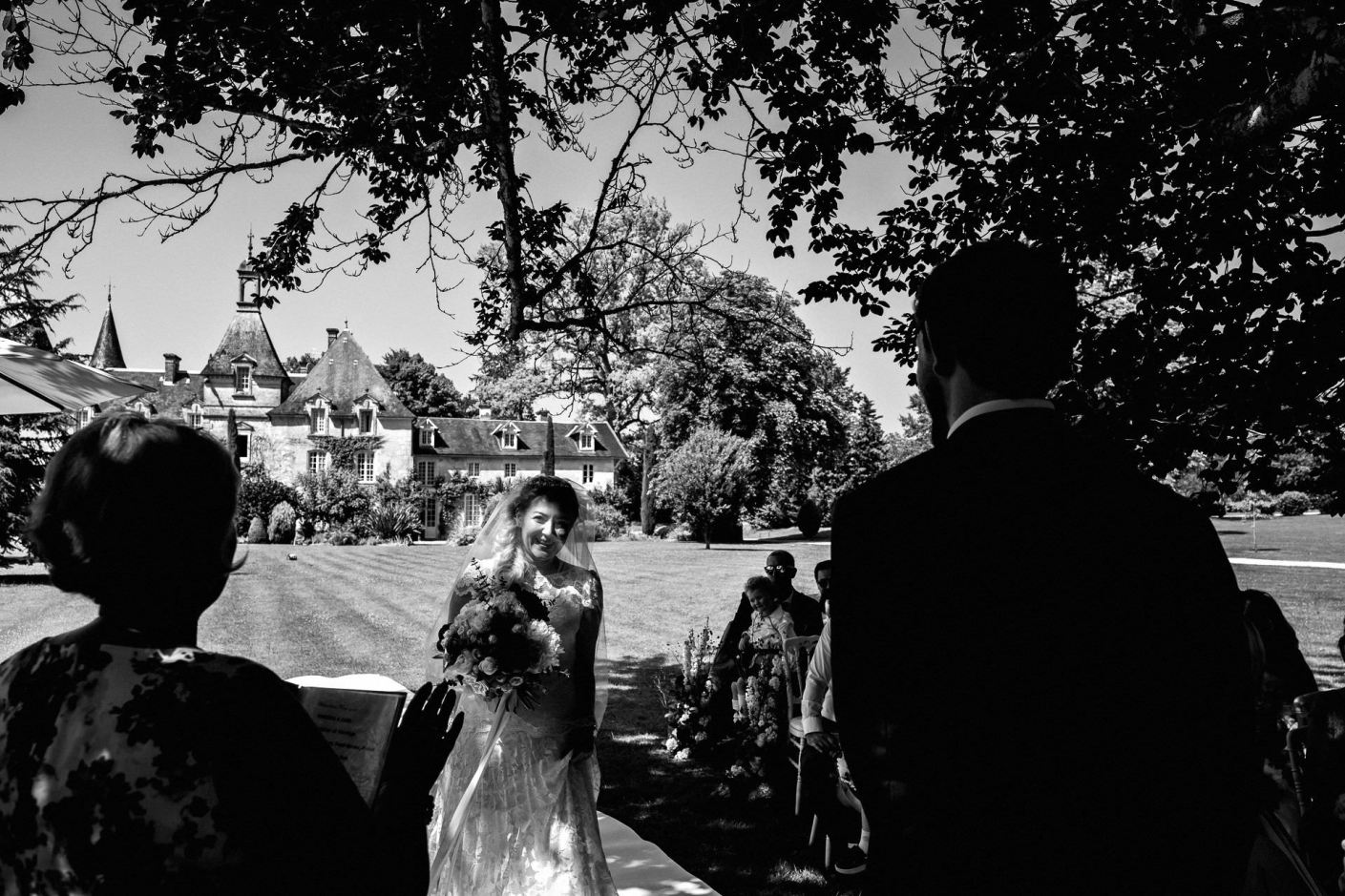 bride arrives to be greeted by the groom under the tree for the wedding