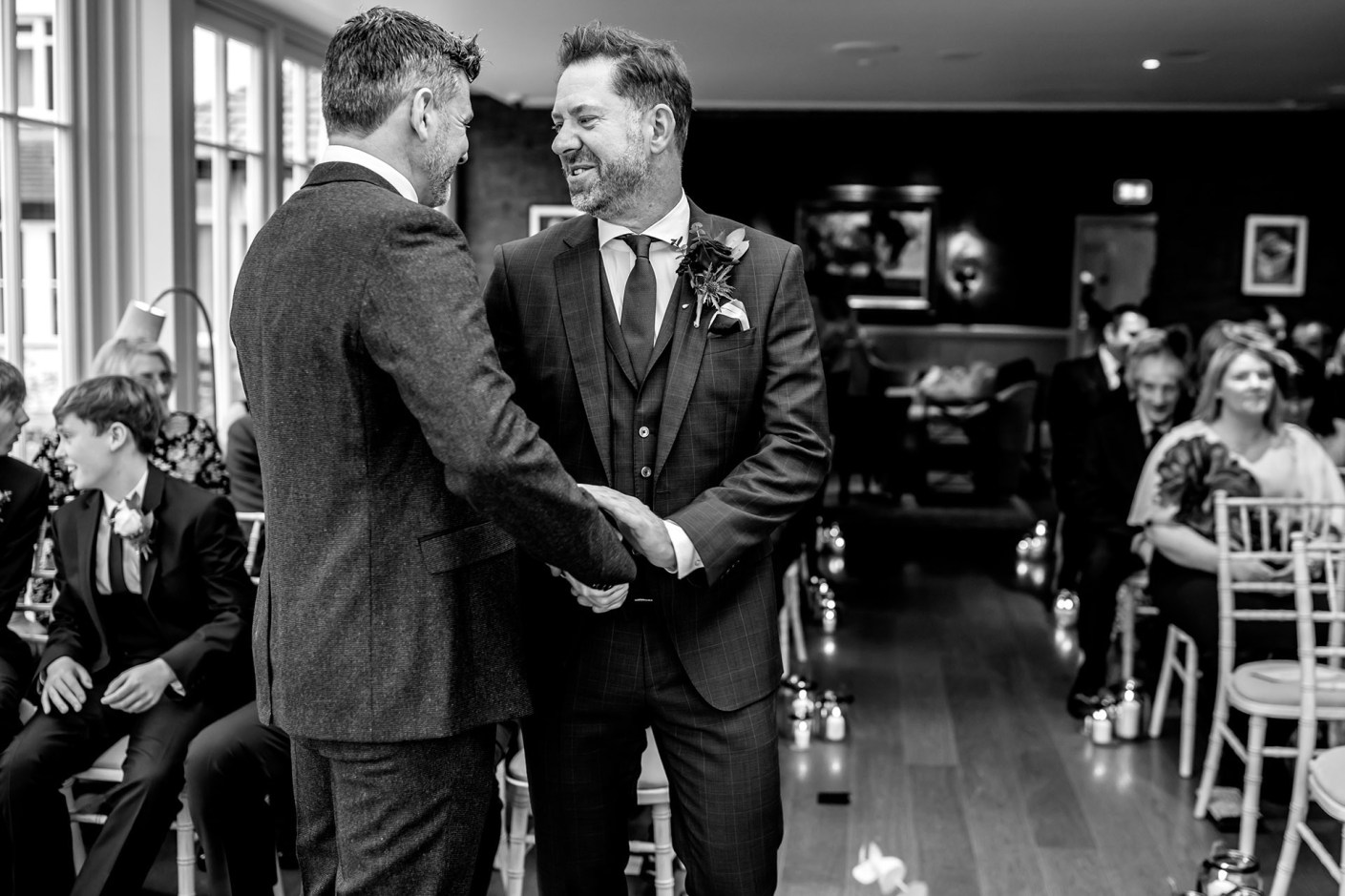 best man and groom shaking hands