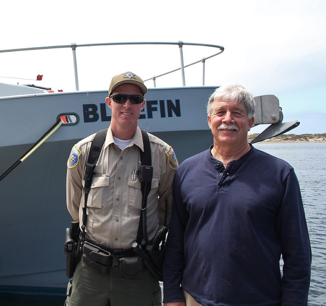 Author Steven T. Callan with Warden Ryan Hanson in front of the Fish and Wildlife Patrol Boat Bluefin