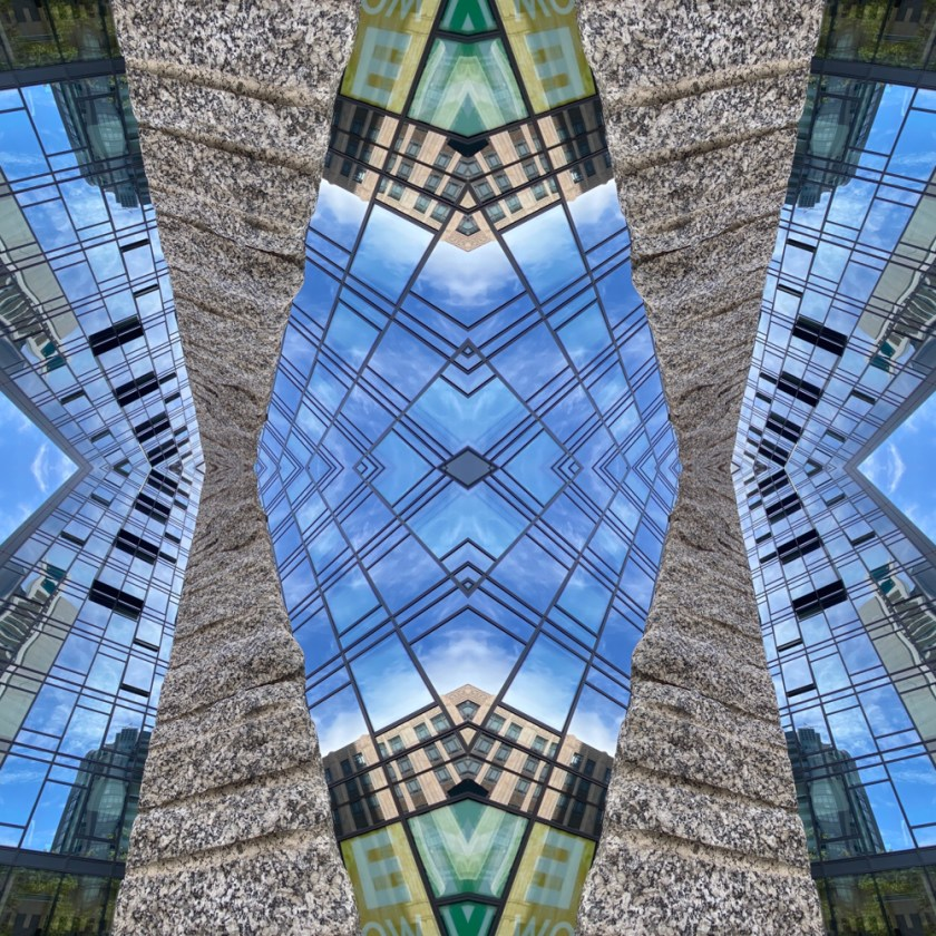 Still image from the video Urban Mandalas. It is the side of building looking up to the sky and the image has been mirrored and repeated to create a mandala effect.