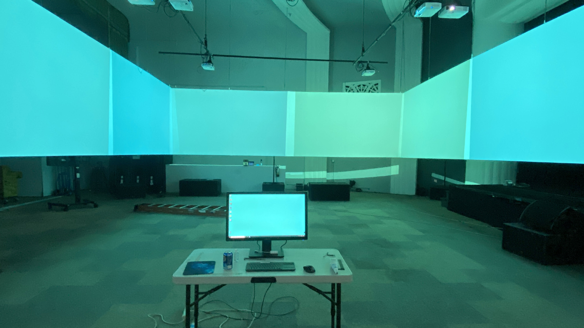 The Cine Chamber during development phase. A computer monitor sits in the middle of the Gray Area Theatre surrounded by video screens. The color projected onto the screens is a light cyan.