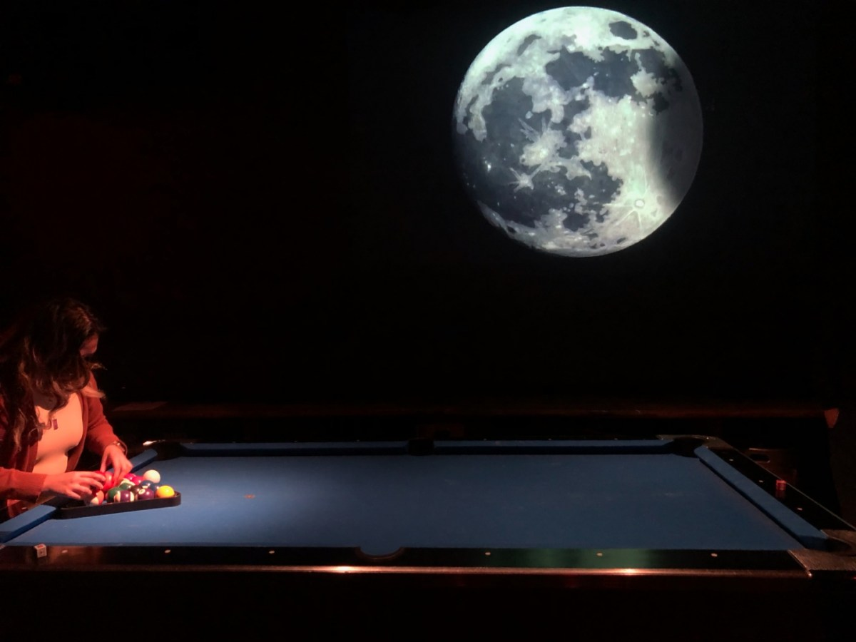 In a dark bar, a pool player is racking the balls, preparing for a game. On the wall behind him, is a video projection map installation of the Moon. It is getting eclipsed with a shadow starting to move across it.