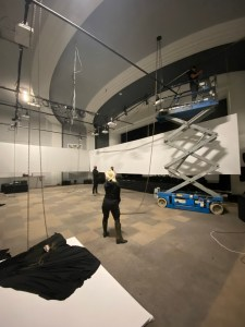 Image of the installation of the Cine Chamber at Gray Area. One man is up in a scissor lift 12 feet in the air securing the screen to the celiing, while 3 people on the floor watch.