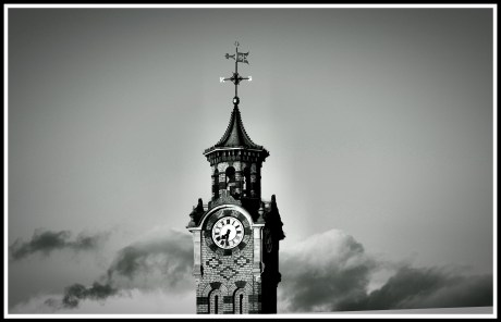 A dramatic black and white photo of the top half of the tower, with rolling dark clouds behind it