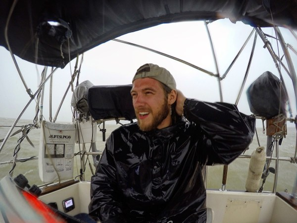 photo of a wet sailor after a squall aboard the boat