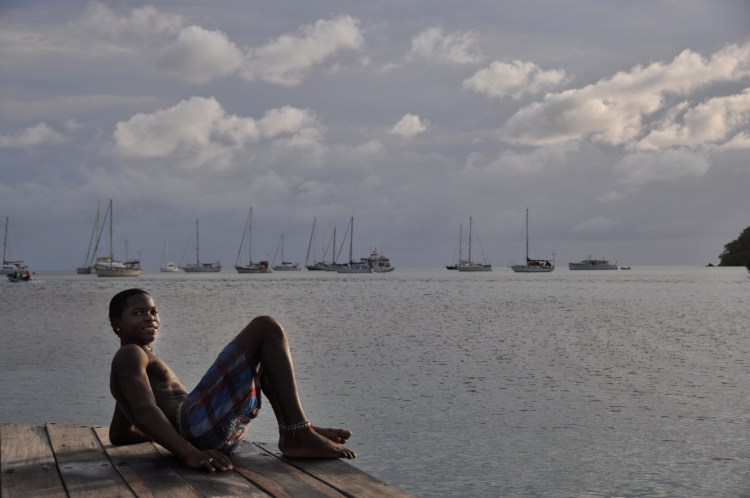 photo of a local colombian boy in providencia with sailboats in the background