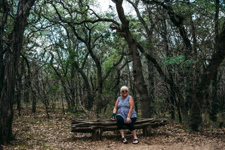 Stevie's mom sitting on a bench at Pedernales Falls State Park outside of Austin Texas