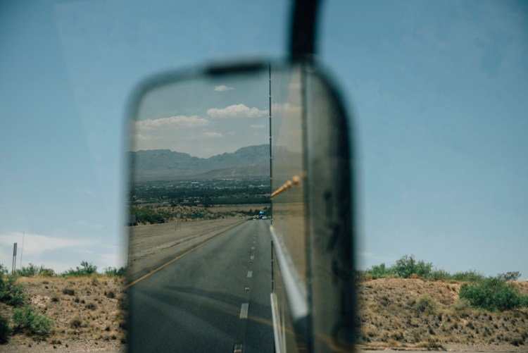 Photo of a side view mirror with Las Cruces, NM in the reflection.