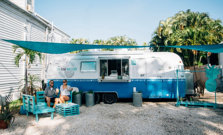 Stevie Vagabond with Olivia in front of The Raw Machine food truck in Key West.