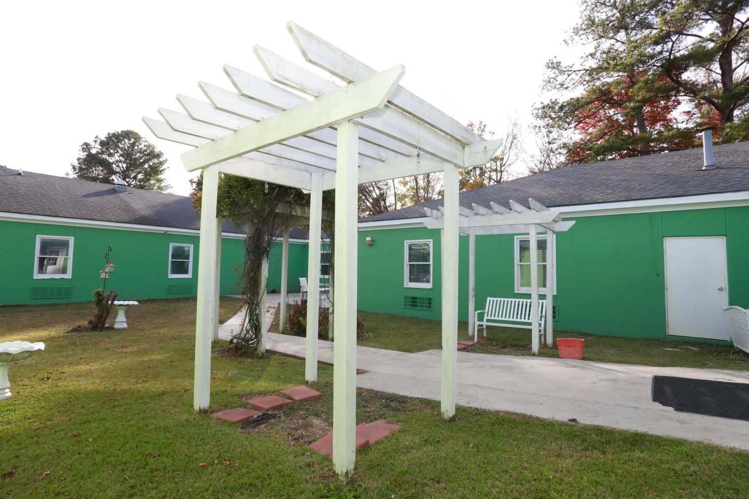 The outside of St. Francis Assisted Living is green. Benches, and bird feeders and baths adorn its lawn.