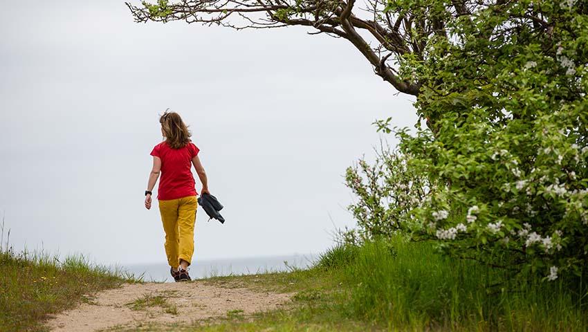 kvinnna gående mot strand
