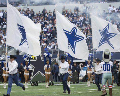 Dallas Cowboys flags display and fans cheering at AT&T Stadium