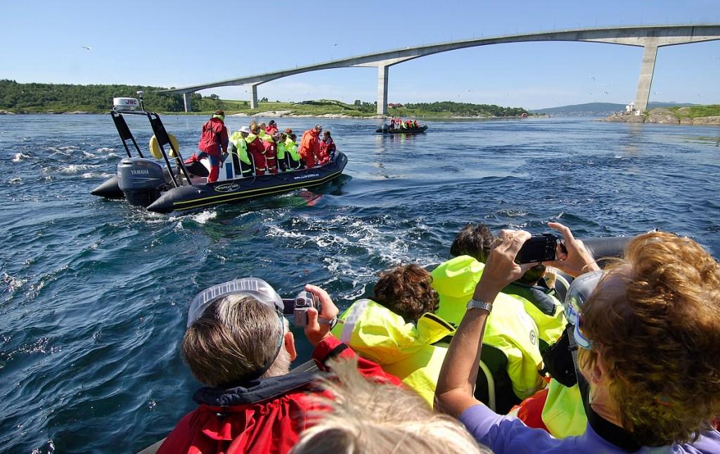 Tre rib-båter på sightseeing i Saltstraumen utenfor Bodø. Båtene er fulle av entusiastiske turister som tar bilder av de sterke strømningene.
