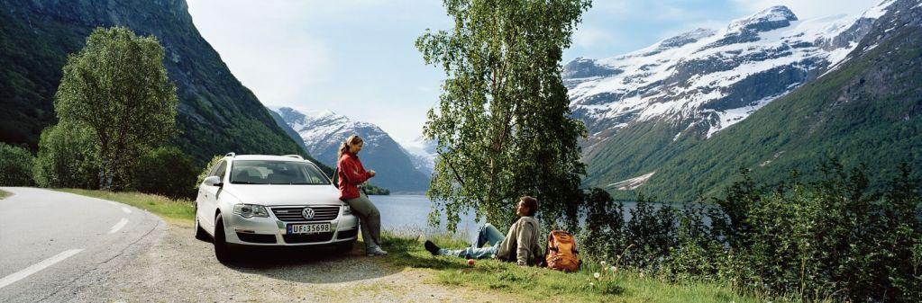 Norge er et vakkert land og godt egnet til en ferie i egen bil. Bildet viser et par som raster i veikanten på vestlandet