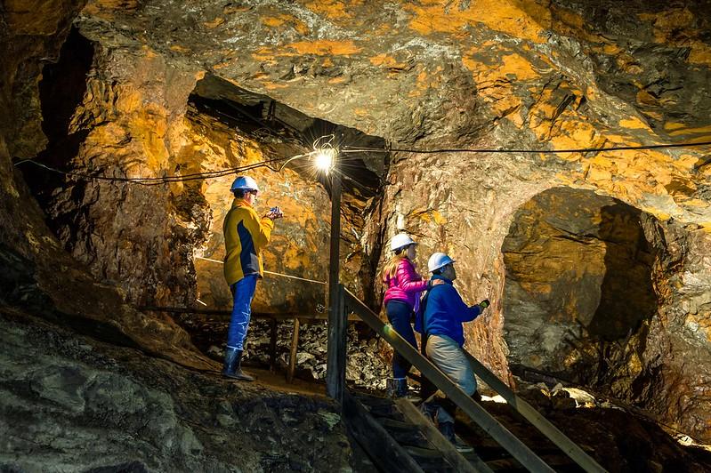 Tre personer med hjelm er på omvisning inne i Olavsgruva på Røros. Magisk lyssetting i gruvegangene.