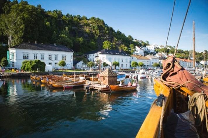 Trebåter i havna i Risør med hvite hus i bakgrunnen. Blå himmel og stille vann.