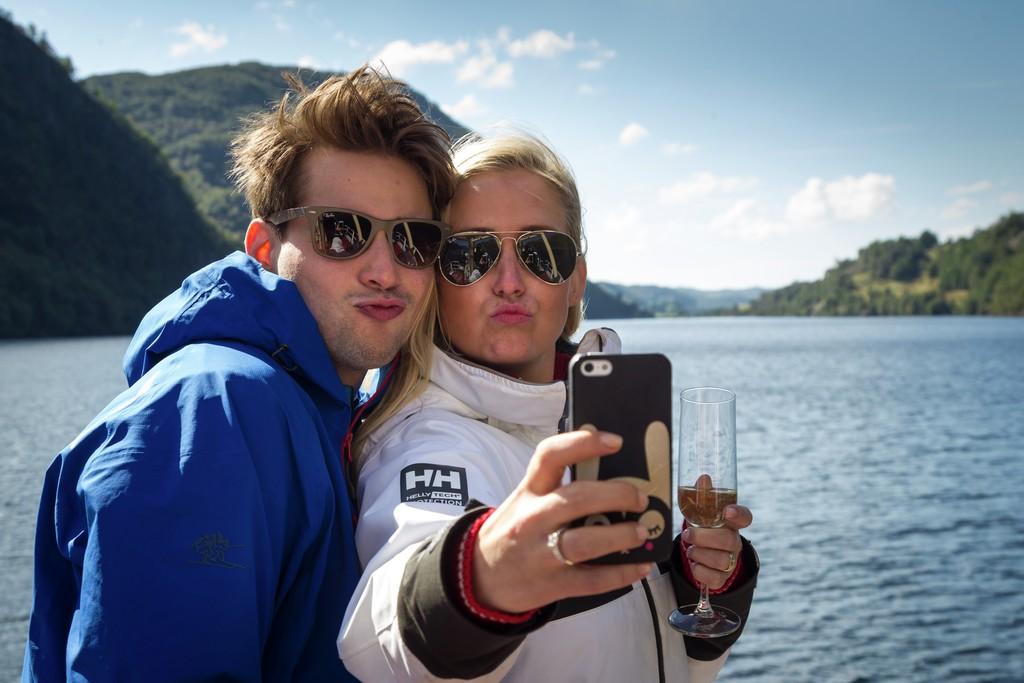 Et ungt par med solbriller tar en selfie på fjordcruise. Champagneglass i hånden.