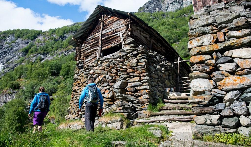 Et voksent par vandrer gjennom Aurlandsdalen. Gammelt stabbur på toppen av en høy gammel steimur.