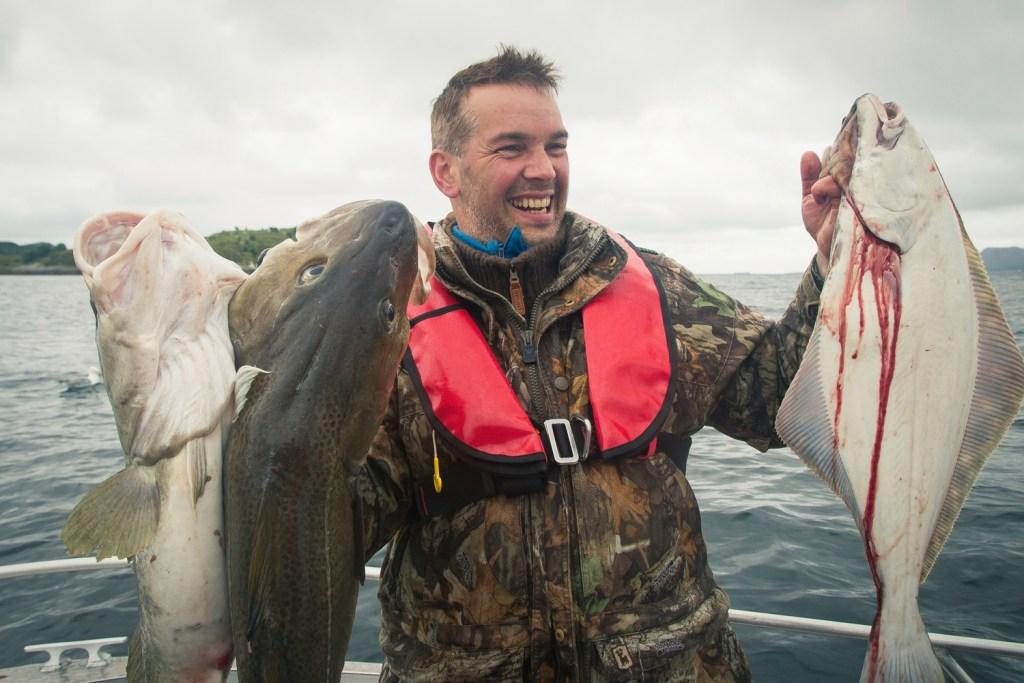 Lykkelig hobbyfisker holder opp tre store fisk for å vise dagens fangst.