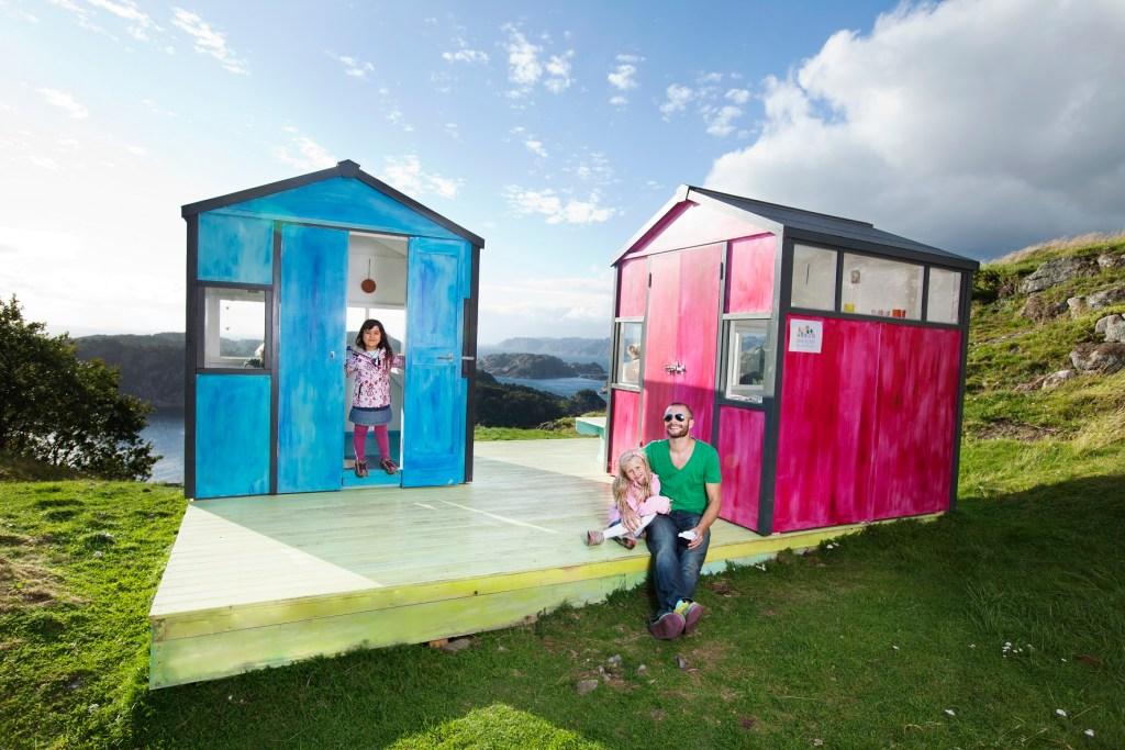 To små hytter som en del av en kunstinstallasjon. En blå og en rød. Pappa med to barn sitter på terrassen.