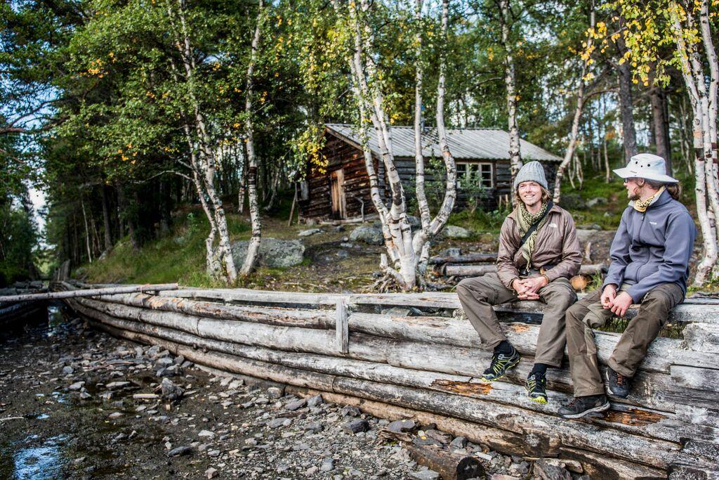To unge gutter i turklær sitter på et tømmergjerde. Gammel tømmerkoie i bakgrunnen.