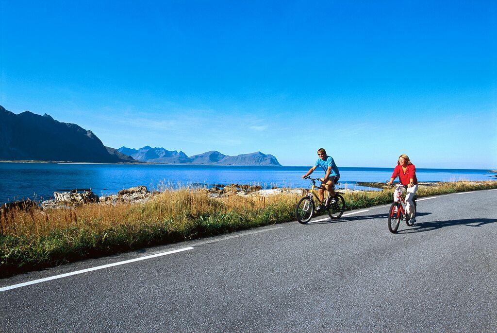 To syklister langs en asfaltert vei i Lofoten. Nydelig natur, blå himmel og fjell i bakgrunnen.