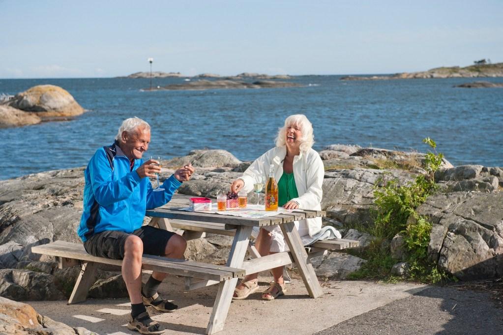 Voksent ektepar på benk i skjærgården på Marivold i Grimstad. Nyter medbrakt mat og drikke.