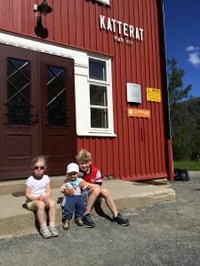Tre barn sitter på trappa til gamle Katterat stasjon. Sol og pent vær.