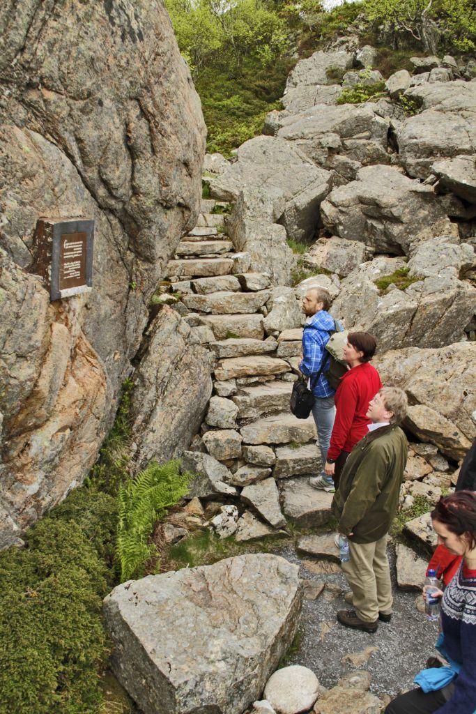 Flere personer på tur opp til Torghatten studerer en informasjonstavle.