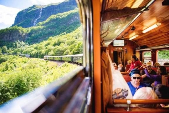 Et tog full av turister på vei opp Flåmsdalen med Flåmsbana. Utsikt fra togvindu.