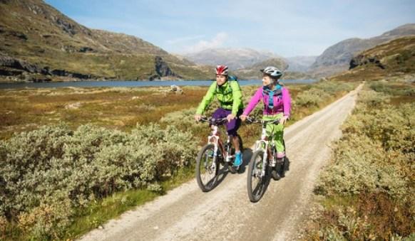 To syklister langs Rallarvegen. Flat grusvei med liten innsjø i bakgrunnen.