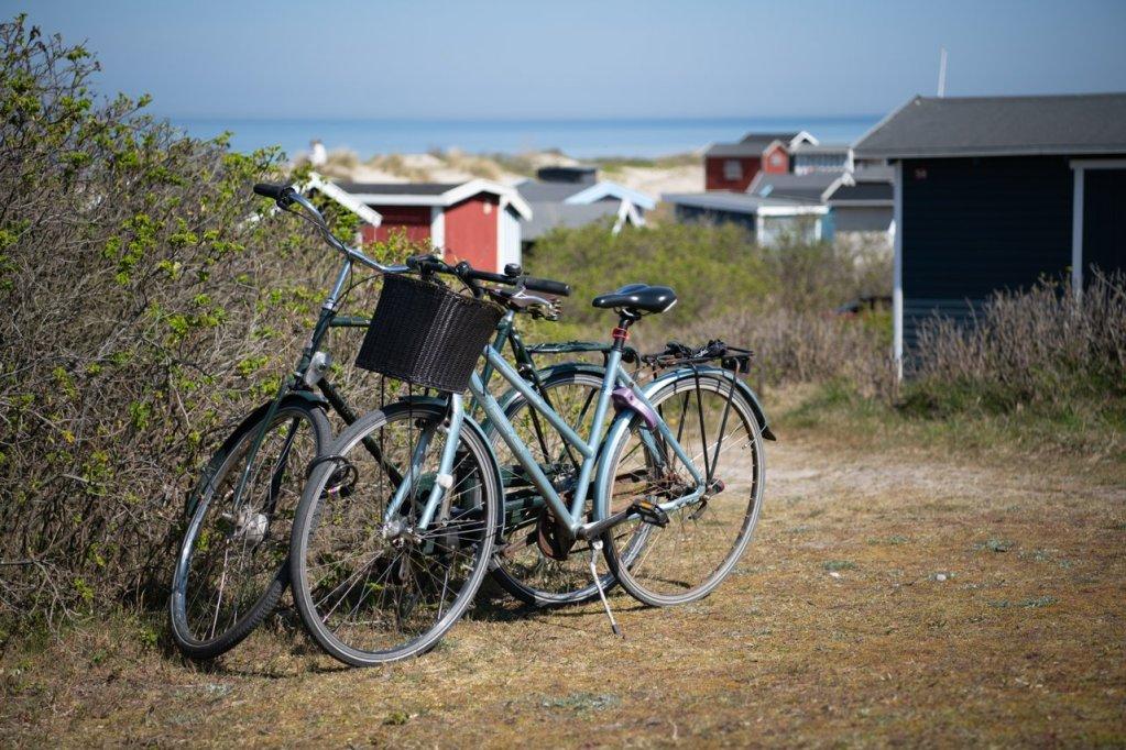 To parkerte sykler på Tilsvilde strand. Mange strandhus og havet i bakrunnen.