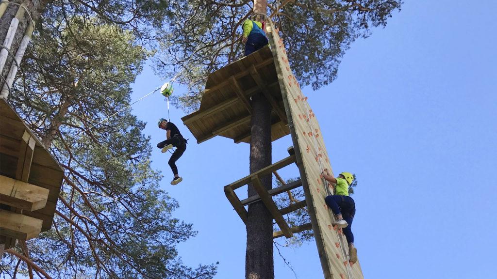 Tre personer i klatrevegg høyt over bakken og som kaster seg ut i en zip-line.