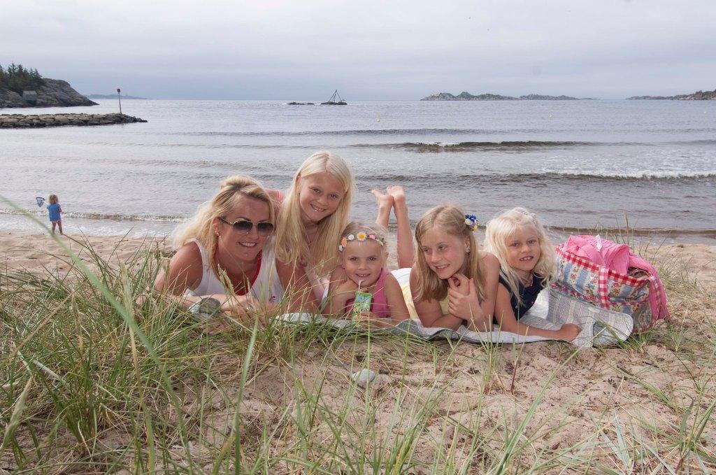 Mor og fire unge jenter ligger på stranda på Sjøsanden i Mandal.