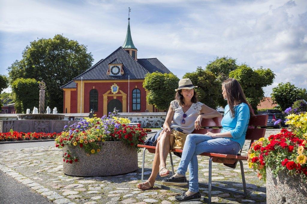 To damer sitter på en benk i Stavern omringet av et blomsterhav i krukker.