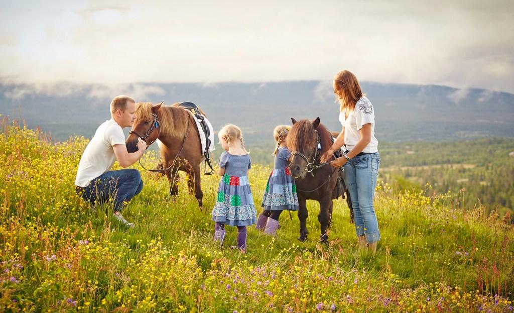 Mor og far med to små jenter står sammen med to hester på Golsfjellet.