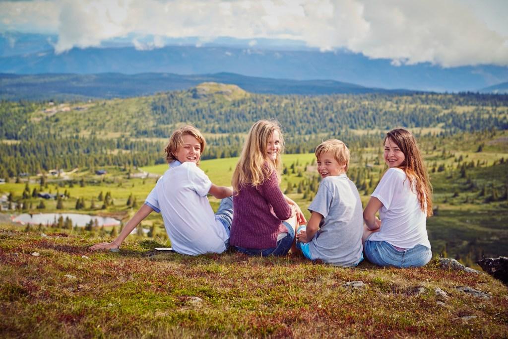 Fire unge mennesker sitter på en kolle og nyter utsikt over Golsfjellet.