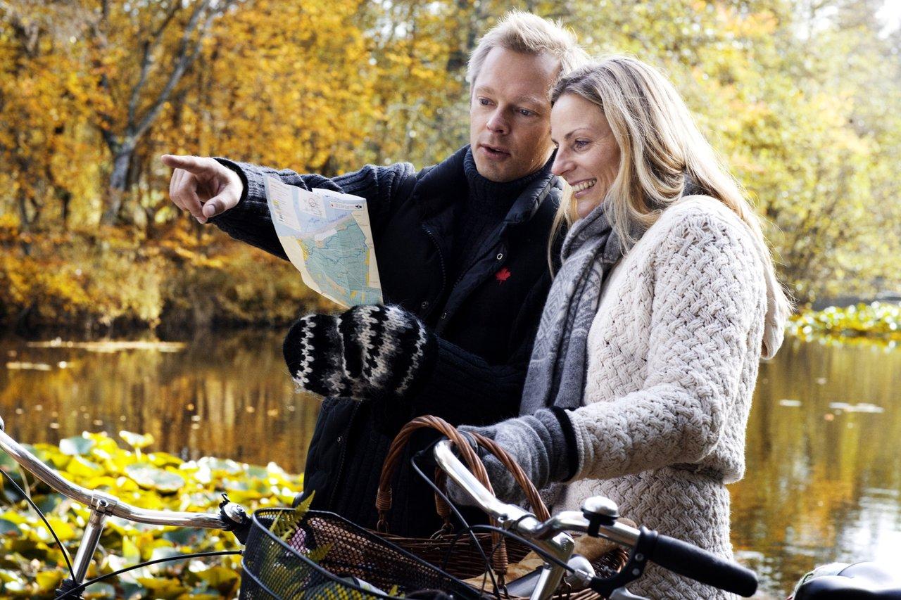 Ungt par på sykkeltur ser på kart