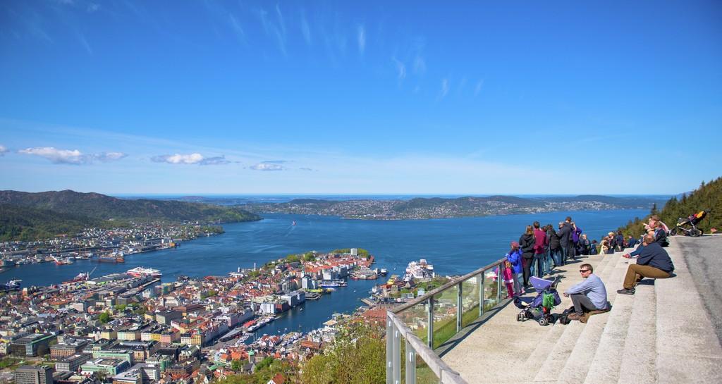 Mange personer sitter i trappa og står ved rekkverket og beundrer utsikt over Bergen fra toppen av Fløyen.