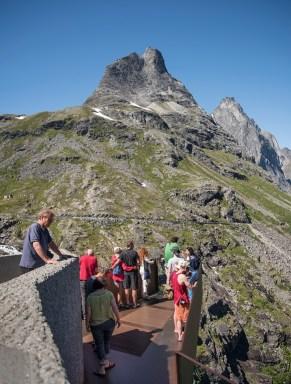 Den store utsiktsplattformen ved Trollstigen byr på enestående utsikt. Mange folk nyter utsikten.